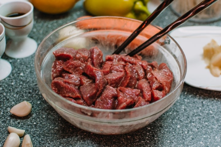 Marinated meat into a plate with garlic and ginger.