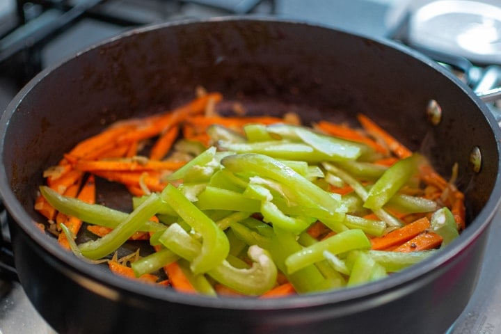 Onions, carrots and bell pepper frying in a pan