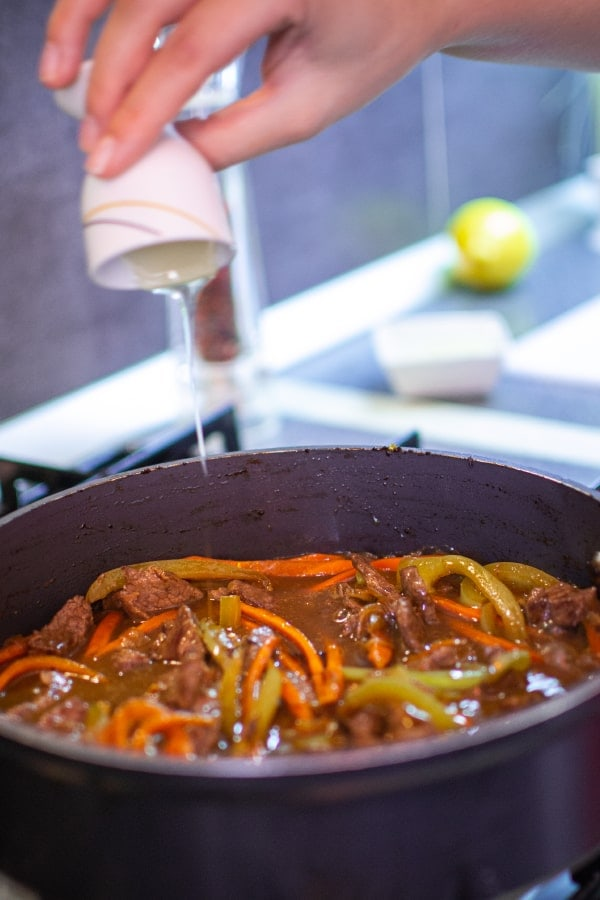 Adding bee honey into pan with meat and vegetables.