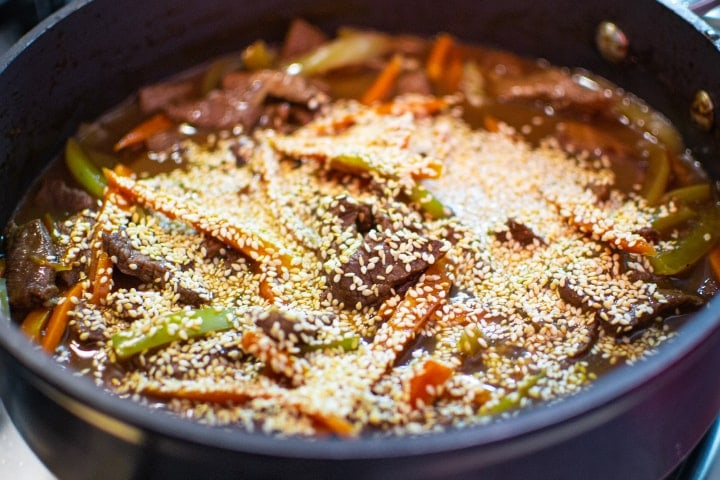 Meat with vegetables and seasame seeds in a pan