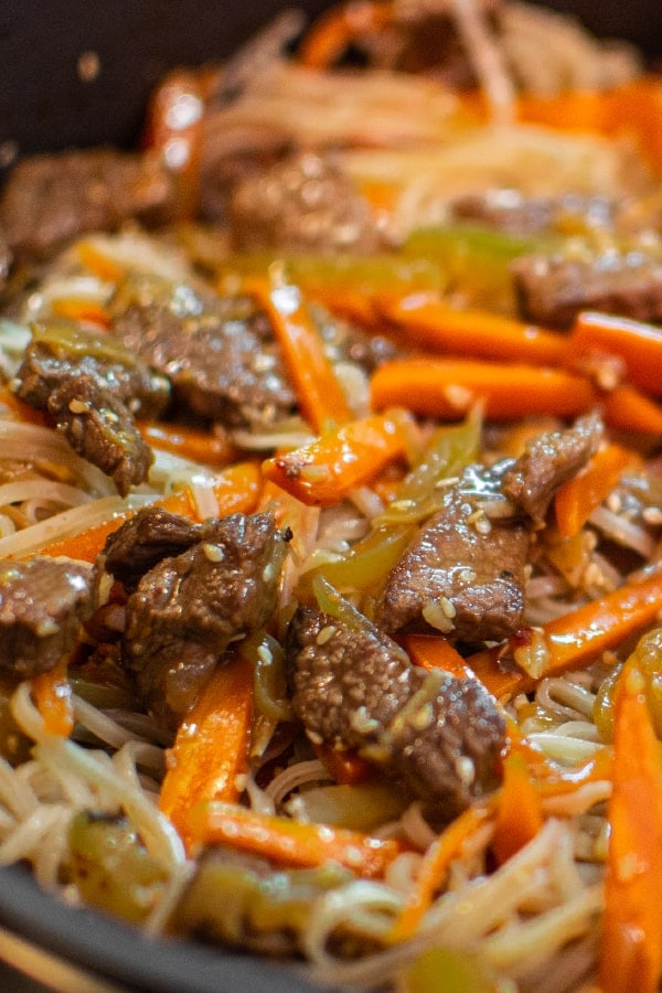 Mix of asian rice noodles with meat, vegetables and seasame seeds.