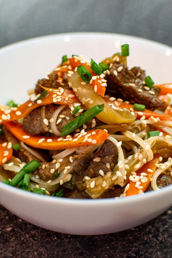 Plate with noodles, vegetables, meat and sesame seeds
