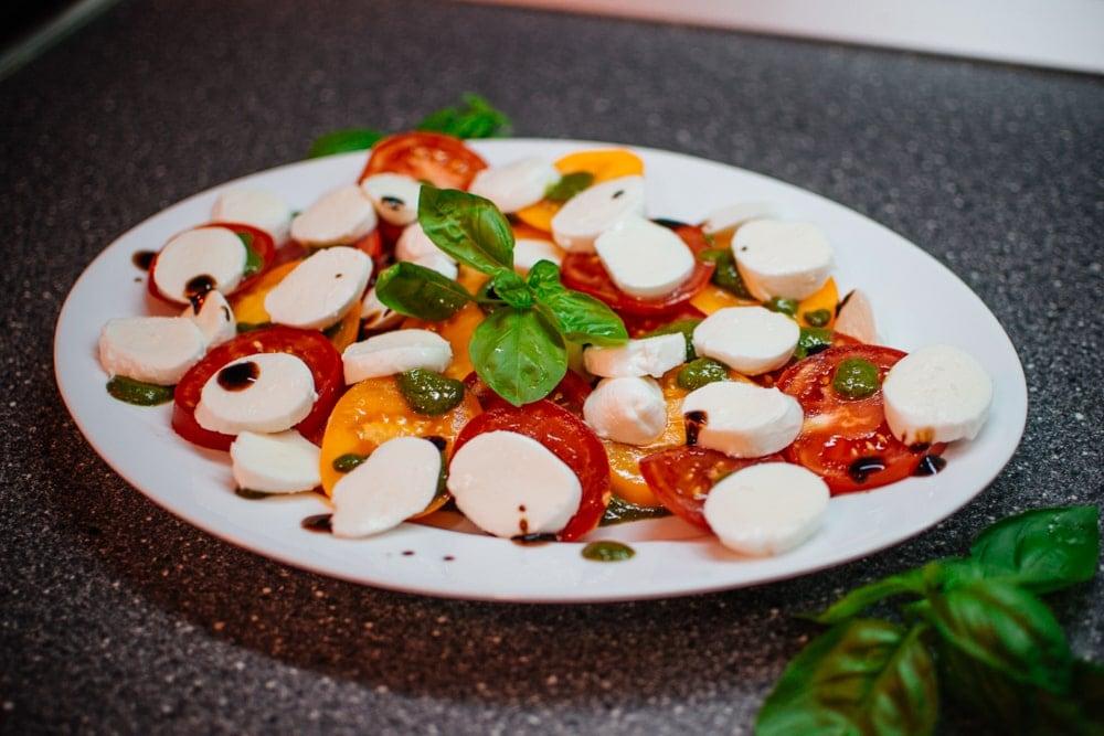 Delicious caprese salad with fresh tomatoes, mozzarella and basil pesto.