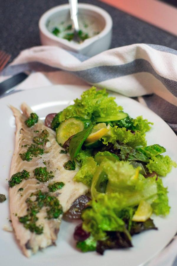 Dorado fish on a white plate with a fresh salad