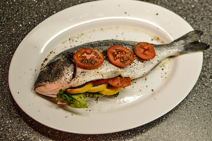 Dorado fish covered with slices of tomatoes on a white plate.