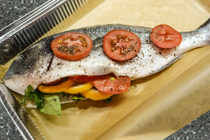 Dorado with with tomatoes in a baking pan