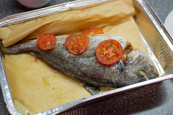 Baked dorado fish with tomatoes.