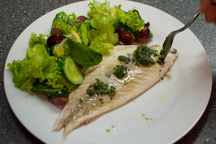 White fillet of a dorado fish with summer salad.