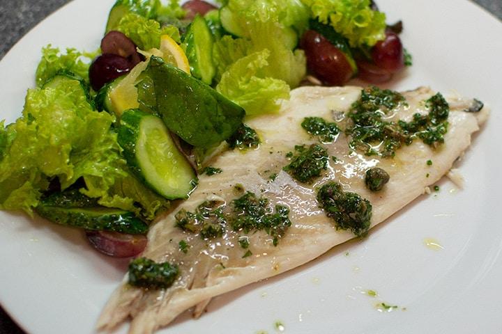 Dorado fish with a summer salad on a plate