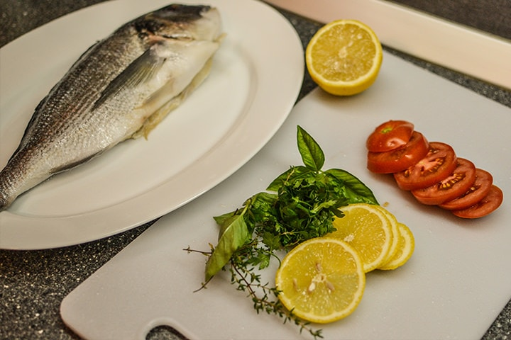 Dorado Fish on a plate with sliced lemons and tomatoes