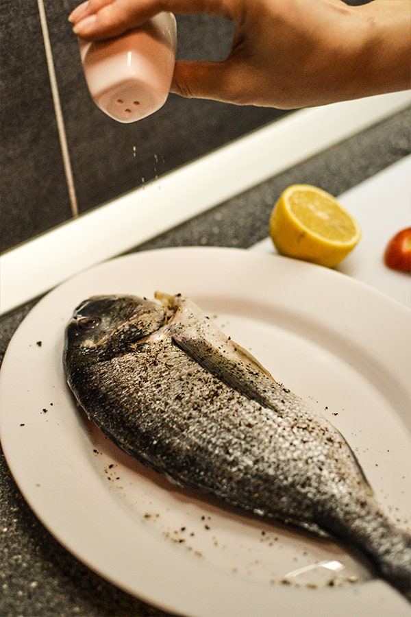 Seasoning a dorado fish with salt and pepper on a white plate.