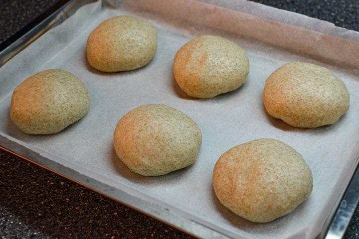6 pieces of burger buns dough on baking pan.