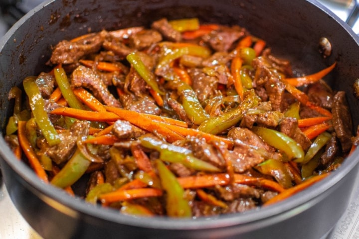 Mix of carrots, onions, bell pepper and meat in a pan