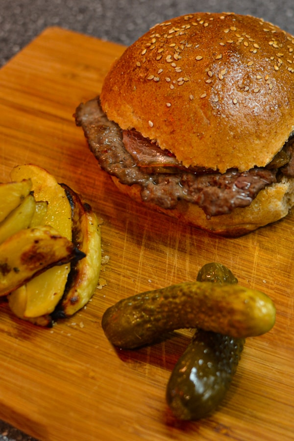 Homemade burger with fried potatoes and cucumbers.