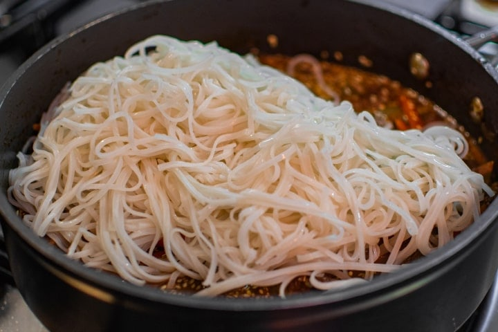 Rice noodles with meat and vegetables in a pan