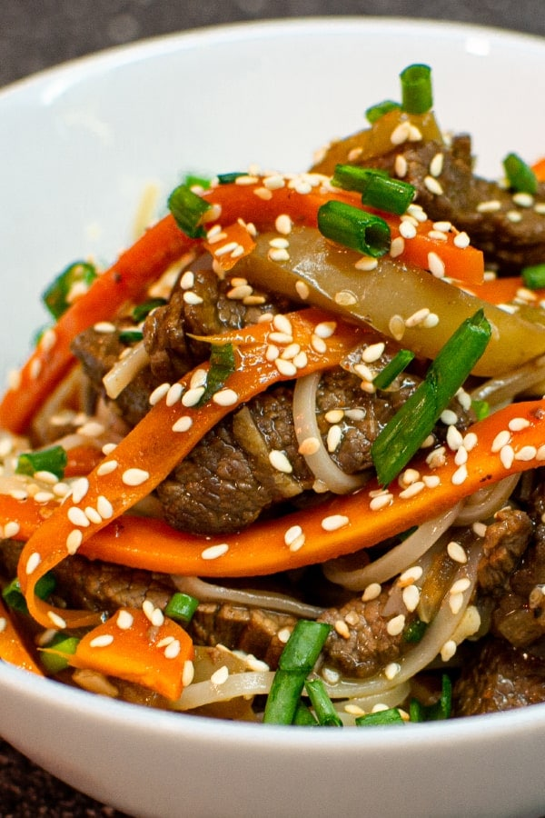 Delicious asian noodles with beef meat and seasame seeds in a bowl
