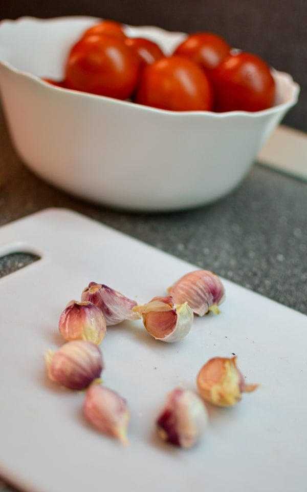 Garlic cloves on a cutting board with tomatoes