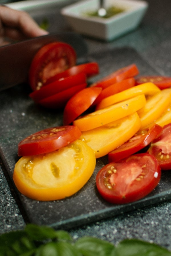 Yellow and red tomatoes on a cutting board.