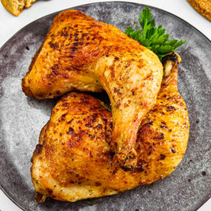 Roasted Chicken Quarters on a gray plate.