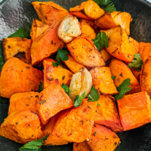 Close view of the sweet potato chunks with garlic and parsley.