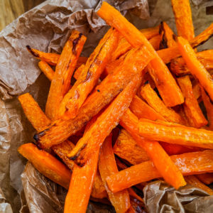 Close view of fried carrot sticks on a perchment paper.
