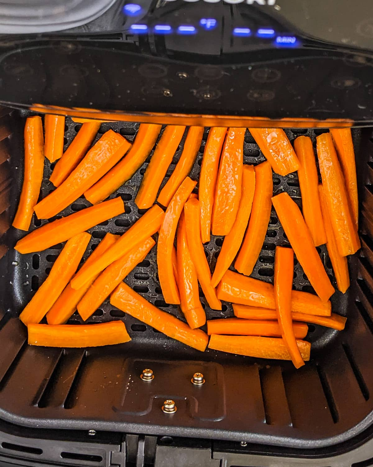 Top view of carrot sticks sprayed with oil.