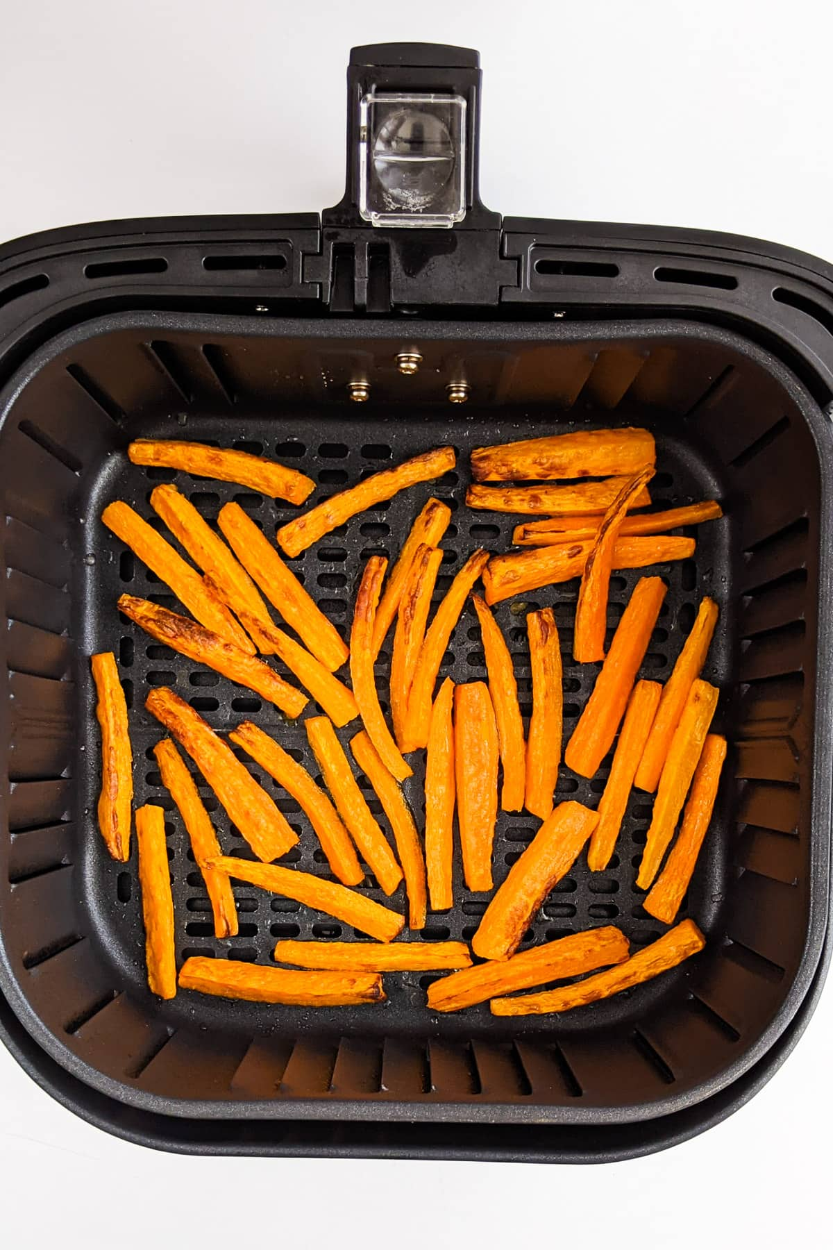 Top view of carrot slices in the air fryer basket.