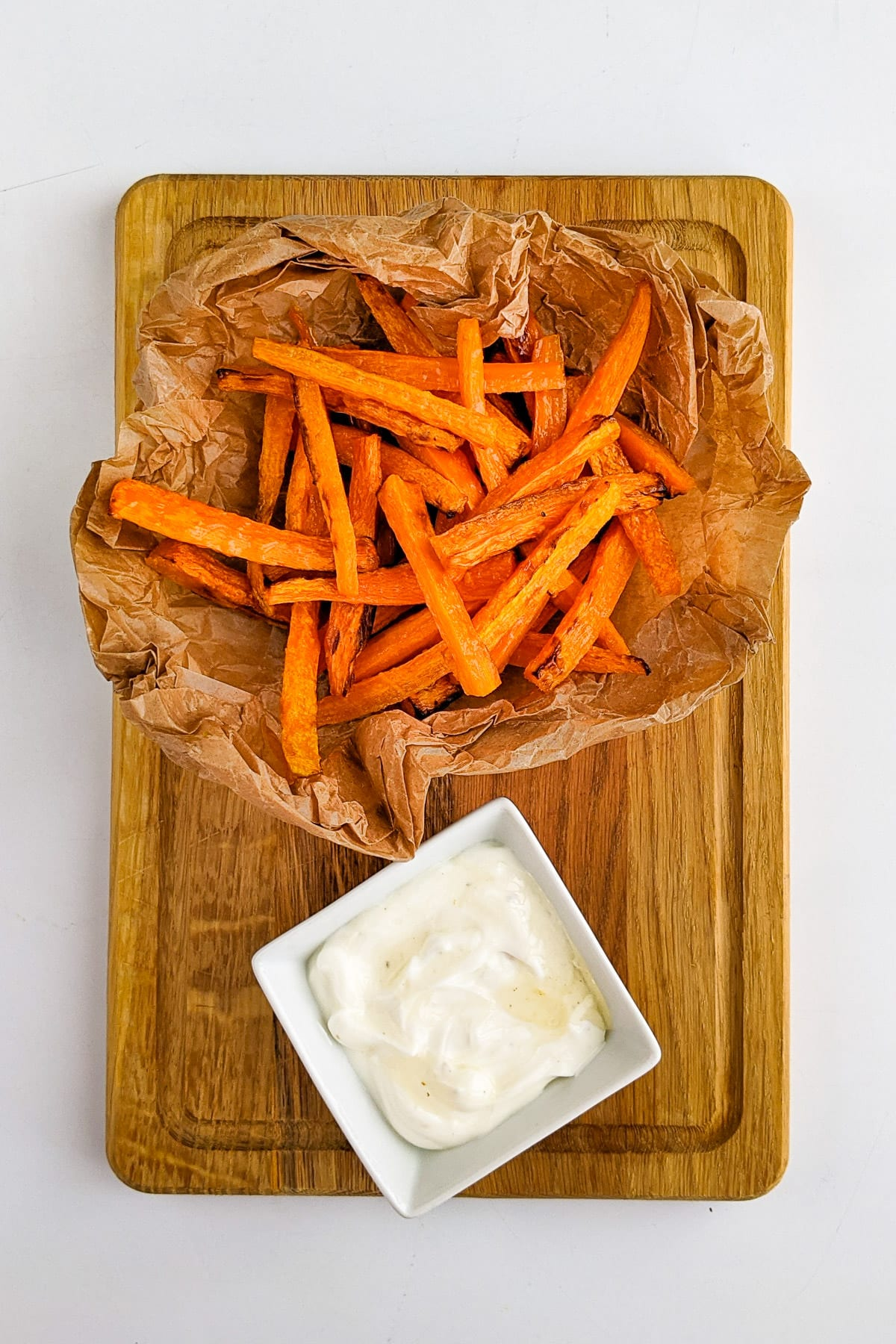 Top view of carrot fries near a white sauce.