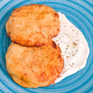 Close look of air fried hash brown patties with sour cream on a blue plate.