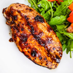Close look at bbq chicken breast near salad leaves.